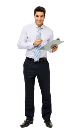 Full length portrait of confident businessman holding clipboard and pen against white background. Vertical shot. photo