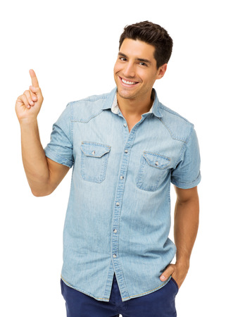Portrait of handsome young man pointing up isolated over white background. Vertical shot. Stock Photo