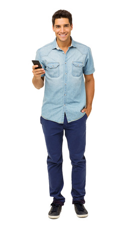 Full length portrait of smiling man holding smart phone against white background. Vertical shot. Stock Photo