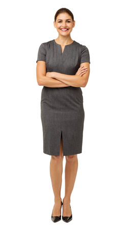 arms crossed: Full length portrait of smiling businesswoman standing arms crossed isolated over white background. Vertical shot. Stock Photo