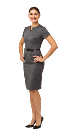 Full length portrait of confident businesswoman with hands on hips standing over white background. Vertical shot. photo