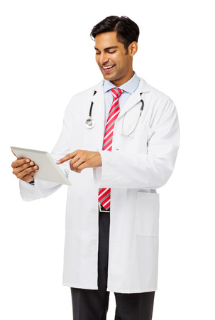 Happy young male doctor using digital tablet against white background. Vertical shot. photo