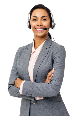 Portrait of confident female customer service representative wearing headset with arms folded against white background. Vertical shot. photo