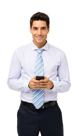 Portrait of confident businessman holding smart phone isolated over white background. Vertical shot.