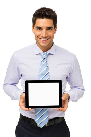 Portrait of confident businessman advertising digital tablet against white background. Vertical shot. Stock Photo