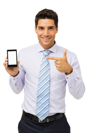 Portrait of smiling businessman pointing at smart phone against white background. Vertical shot.