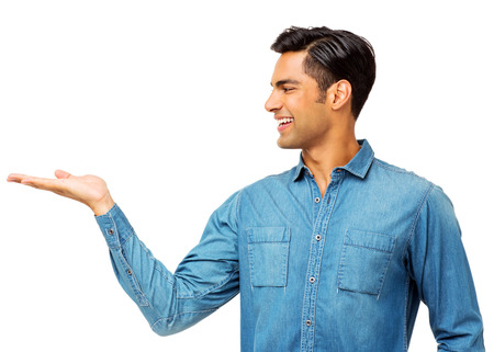Smiling Indian man holding invisible product over white background. Horizontal shot.