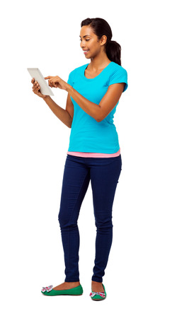 Full length of young woman using digital tablet over white background. Vertical shot. Stock Photo