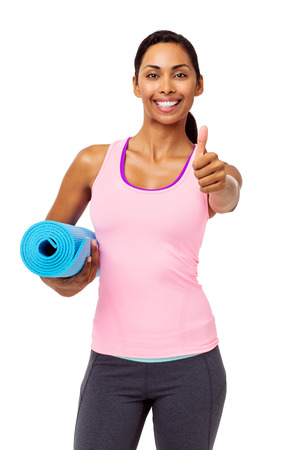 Portrait of confident fit woman gesturing thumbs up while holding exercise mat over white background. Vertical shot.