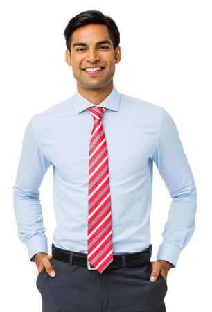 portrait view: Portrait of happy businessman with hands in pockets standing against white background. Vertical shot. Stock Photo
