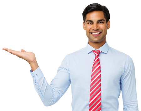 Portrait of happy young businessman presenting invisible product against white background. Horizontal shot. Stock Photo