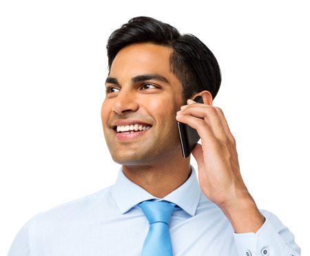 Smiling businessman looking away while answering smart phone against white background. Horizontal shot.