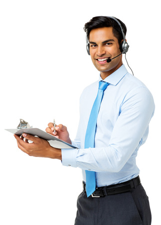 Portrait of happy male call center representative writing on clipboard and wearing headset against white background. Vertical shot. photo