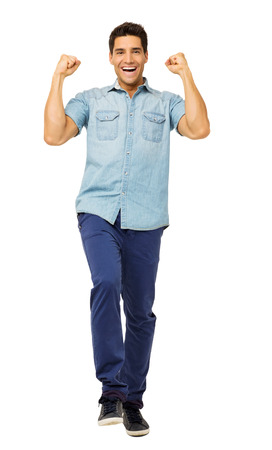 Full length portrait of successful young man celebrating success over white background. Vertical shot. photo