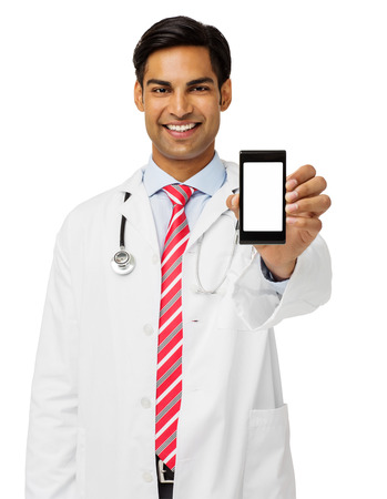 Portrait of smiling male doctor showing smart phone standing against white background. Vertical shot.