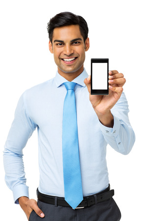Portrait of confident businessman showing smart phone while standing over white background. Vertical shot. photo