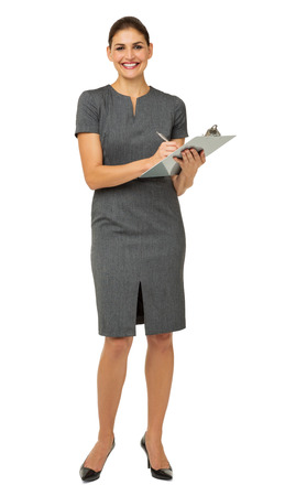 one mid adult woman only: Full length portrait of happy businesswoman holding clipboard and pen against white background. Vertical shot.