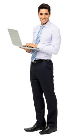 Full length portrait of smiling businessman with laptop standing isolated over white background. Vertical shot. Stock Photo