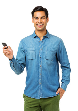 Portrait of confident young man using smart phone over white background. Vertical shot. Stock Photo