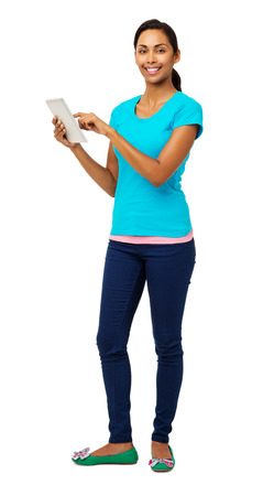 Full length portrait of confident young woman using digital tablet over white background. Vertical shot. photo