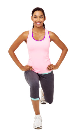 Full length portrait of smiling young woman performing stretching lunge exercises over white background. Vertical shot.