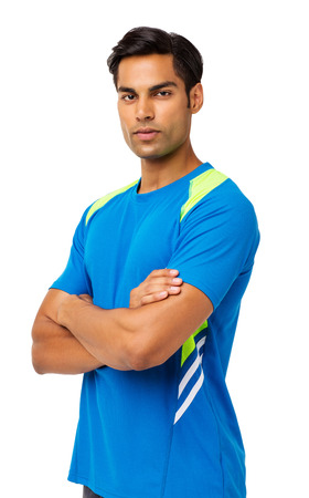 Portrait of confident young man in sports clothing standing against white background. Vertical shot.