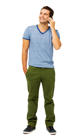 Full length of handsome young man answering smart phone isolated over white background. Vertical shot.