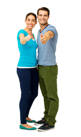 Full length portrait of happy couple showing thumbs up sign over white background. Vertical shot.