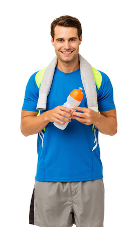 Portrait of happy young man with towel and water bottle standing isolated over white background. Vertical shot. photo