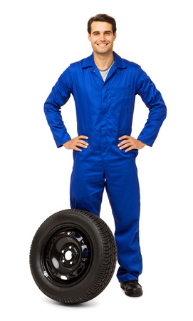 Full length portrait of confident male mechanic with spare tire standing isolated over white background. Vertical shot.