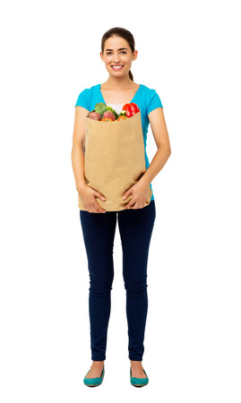 Full length portrait of beautiful young woman holding vegetables bag isolated over white background. Vertical shot. photo