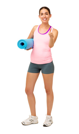 Full length portrait of happy young woman with exercise mat gesturing thumbs up over white background. Vertical shot. photo