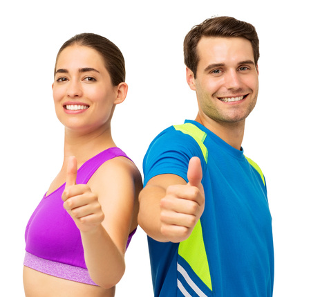 Portrait of happy young couple in sports wear gesturing thumbs up over white background. Horizontal shot. photo