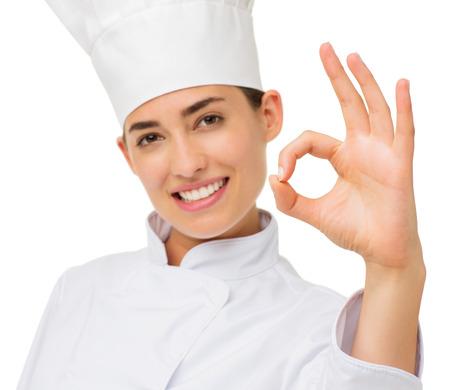 Portrait of happy female chef showing OK sign over white background. Horizontal shot. photo