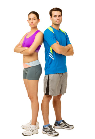 Full length portrait of confident young couple in sports wear standing back to back over white background. Vertical shot. photo