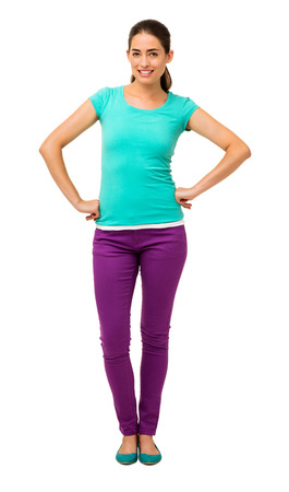 Full length portrait of young woman in casuals standing with hands on hips isolated over white background. Vertical shot. photo