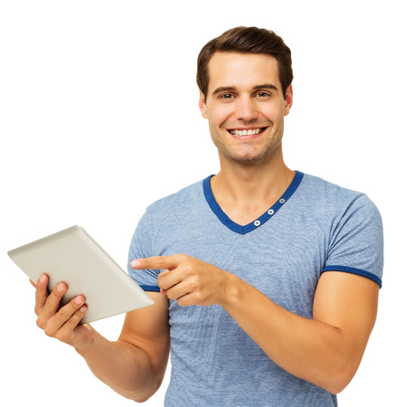Portrait of happy young man pointing at digital tablet isolated over white background. Horizontal shot. photo