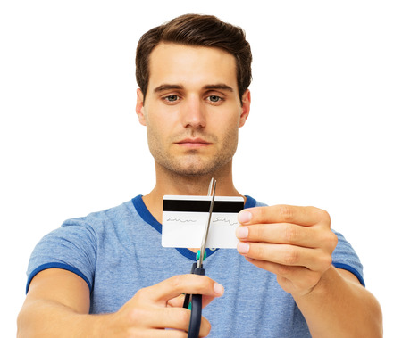 Serious young man cutting credit card with scissor over white background. Horizontal shot. photo