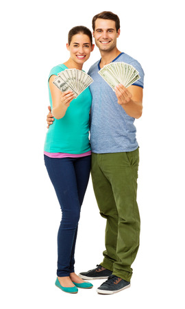 Full length portrait of happy young couple holding fanned US banknotes over white background. Vertical shot. Stock Photo