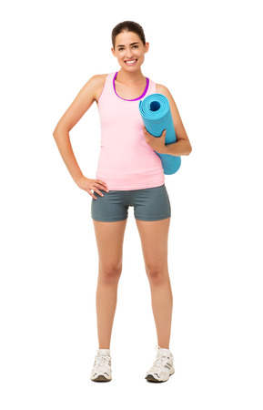 Full length portrait of confident young woman holding rolled up exercise mat over white background. Vertical shot. photo