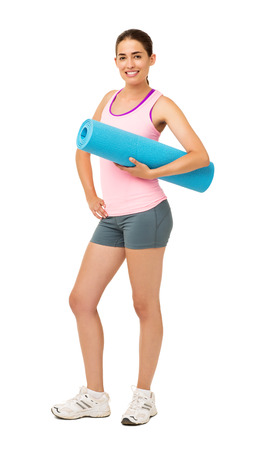 Portrait of happy young woman holding yoga mat over white background. Vertical shot. photo