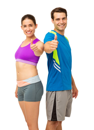 Portrait of happy young couple in sports wear gesturing thumbs up over white background. Vertical shot. Stock Photo