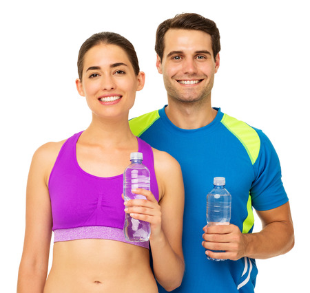 Portrait of happy fit couple in sports wear holding water bottles over white background. Horizontal shot. photo