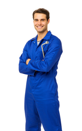 Portrait of handsome male mechanic in overalls holding wrench over white background. Vertical shot.
