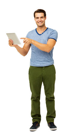 Full length portrait of handsome man pointing at digital tablet isolated over white background. Vertical shot. photo