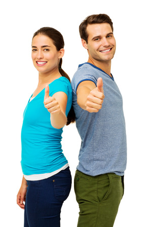 Side view portrait of happy couple showing thumbs up sign while standing back to back over white background. Vertical shot.