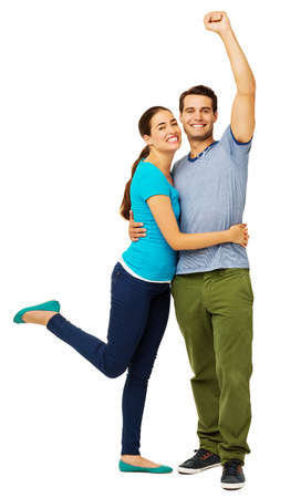 Full length portrait of successful couple embracing against white background. Vertical shot.