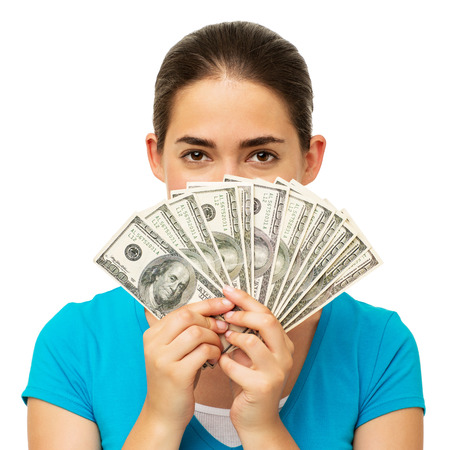Portrait of young woman holding fanned out dollars in front of face over white background. Horizontal shot. photo
