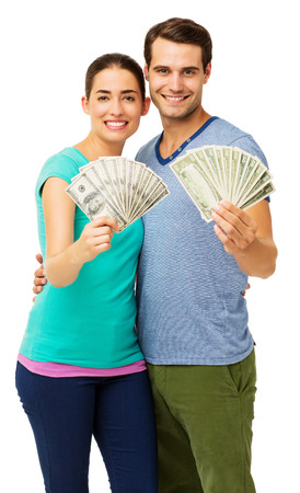 Portrait of happy young couple holding fanned US paper currency over white background. Vertical shot.