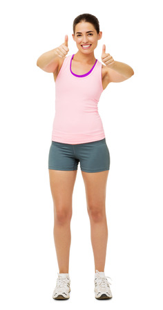 Full length portrait of happy young woman in sportswear gesturing thumbs up over white background. Vertical shot. Stock Photo - 27276369